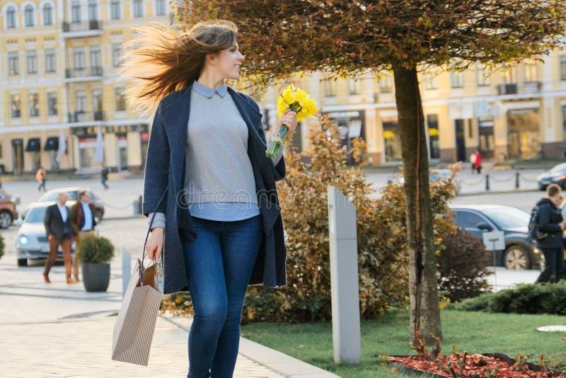 Portrait de belle fille marchant dans la ville, la jeune femme avec le bouquet des fleurs jaunes et le sac ? provisions, ville de photos stock