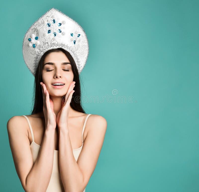 Portrait de belle fille mignonne dans le chapeau de kokoshnik envoyant le baiser de soufflement avec des lèvres de tacaud regarda photo stock