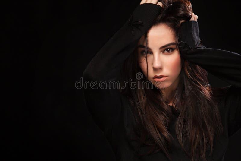 Portrait de belle fille sexy de brunnete, sur le fond noir Joli modèle de fille Une femme de brune dans une robe noire photo libre de droits