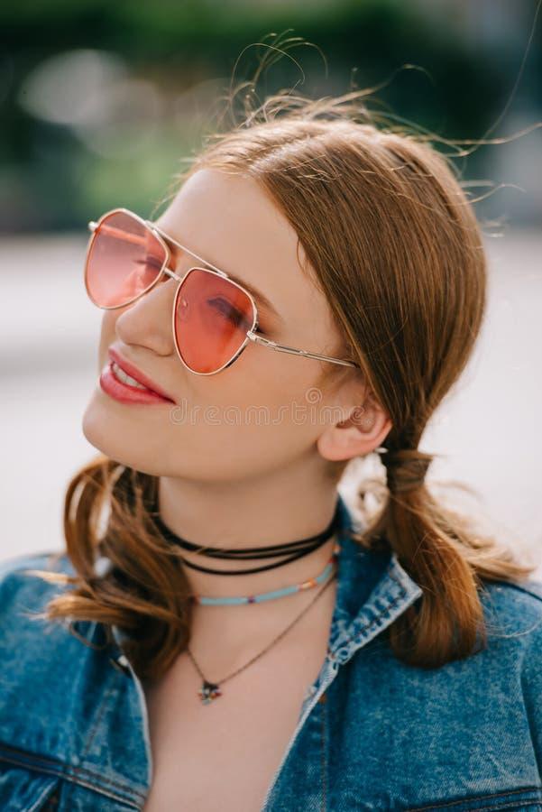 portrait de belle fille de sourire dans les lunettes de soleil et le regard de veste de denim photographie stock
