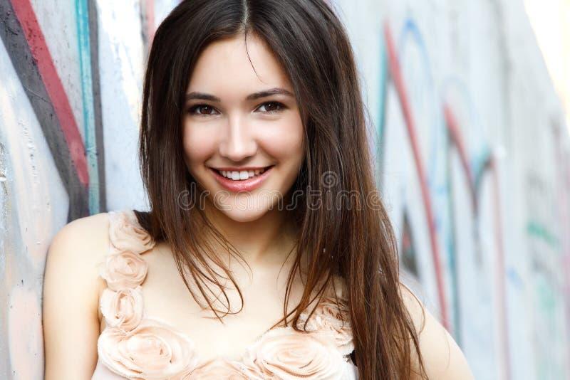 Portrait de belle fille de sourire de mode contre le mur avec de l'ABS photographie stock