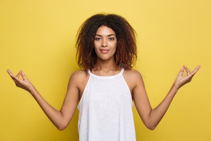 Portrait de belle jeune femelle calme de noir d'afro-américain avec du yoga de pratique de coiffure d'Afro à l'intérieur, méditan image libre de droits