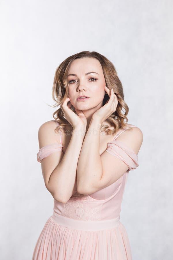 Portrait de belle jeune femelle ?l?gante dans p?le - robe l'?pousant rose avec la grande encolure, sur un fond blanc photo libre de droits