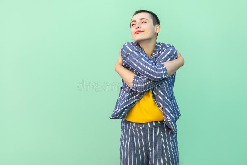 Portrait de belle jeune femme élégante belle heureuse de cheveux courts dans la position rayée occasionnelle de costume s'étreign images libres de droits