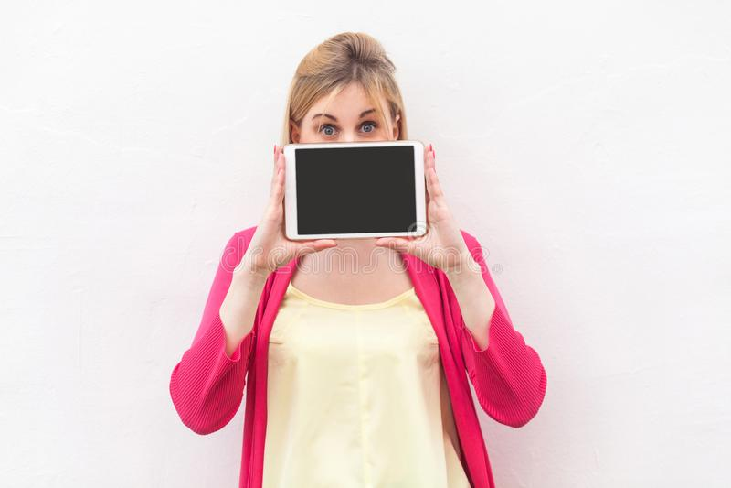 Portrait de belle jeune femme étonnée dans la position rose et tenir l'écran vide de comprimé, le couvert de la bouche et la rega photographie stock