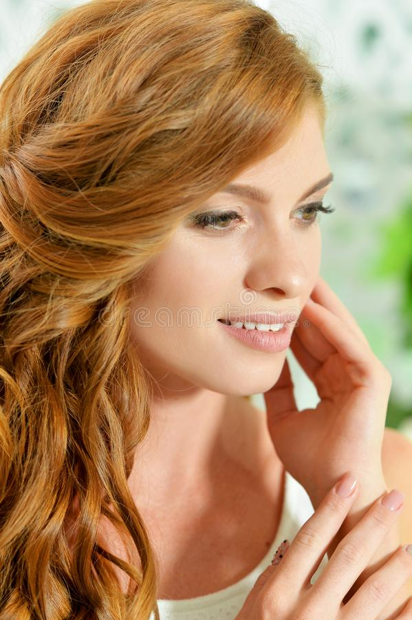 Portrait de belle jeune femme avec les cheveux rouges posant à la maison image libre de droits