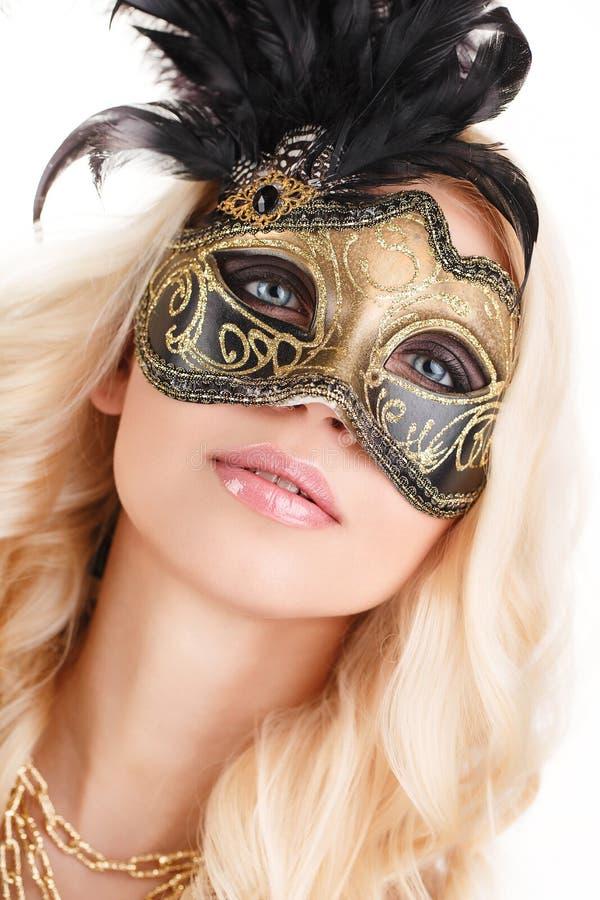 Portrait de belle jeune femme blonde dans le noir et le masque vénitien mystérieux d'or. Photo de mode sur le fond blanc images stock