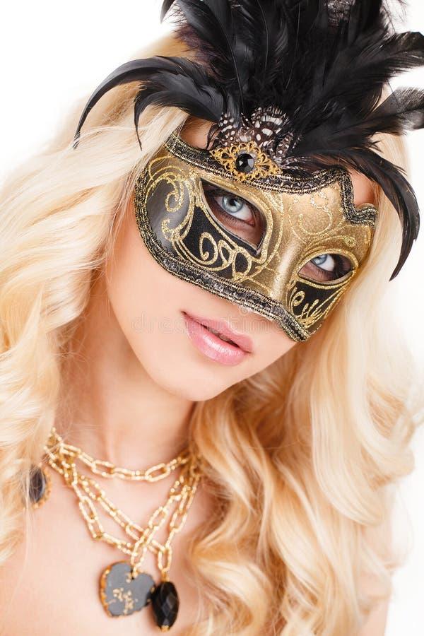 Portrait de belle jeune femme blonde dans le noir et le masque vénitien mystérieux d'or. Photo de mode sur le fond blanc images libres de droits