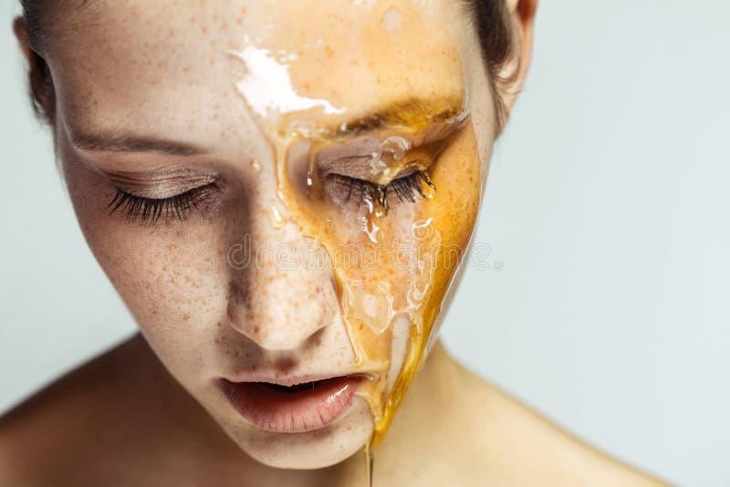 Portrait de belle jeune femme de brune avec les taches de rousseur et le miel sur le visage avec les yeux fermés et le visage sér photographie stock