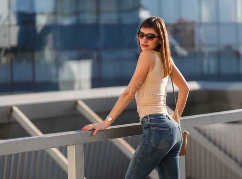 Portrait de belle jeune femme de brune dans la chemise, les jeans de denim et des lunettes de soleil beiges int?ressants Sac en c image libre de droits