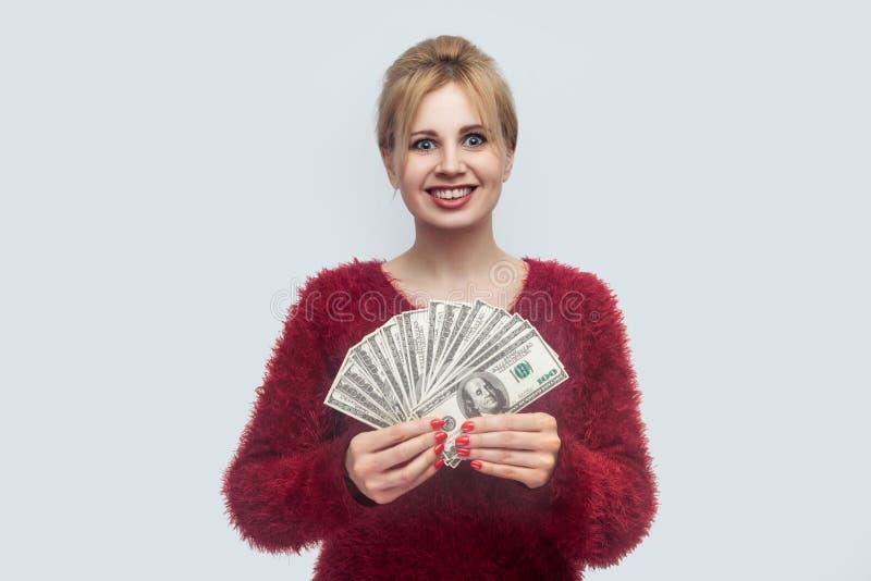 Portrait de belle jeune femme d'affaires dans le chemisier rouge tenant, tenant et démontrant la fan de l'argent et regardant la  photos stock