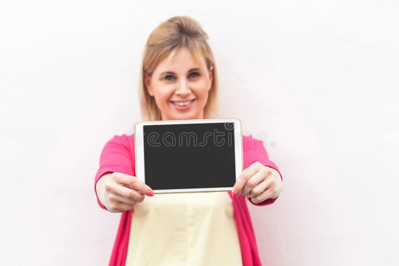 Portrait de belle jeune femme d'affaires heureuse dans la position rose et tenir de chemisier l'écran vide de comprimé avec le so photo libre de droits