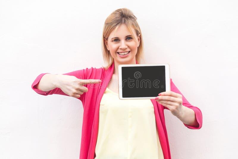 Portrait de belle jeune femme d'affaires satisfaisante à la position rose et à tenir l'écran vide de comprimé et à indiquer de ch images stock