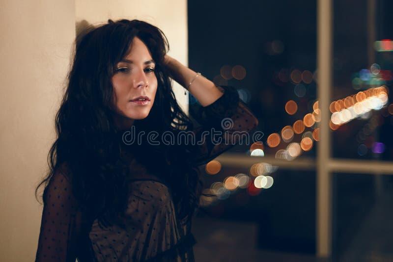 Portrait de belle jeune femme dans la robe de cocktail noire se penchant sur le mur photos stock
