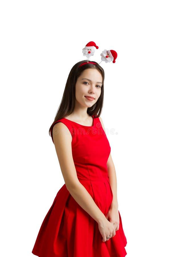 Portrait de belle jeune femme dans la robe rouge jugeant le boîte-cadeau d'isolement au-dessus du fond blanc photo stock