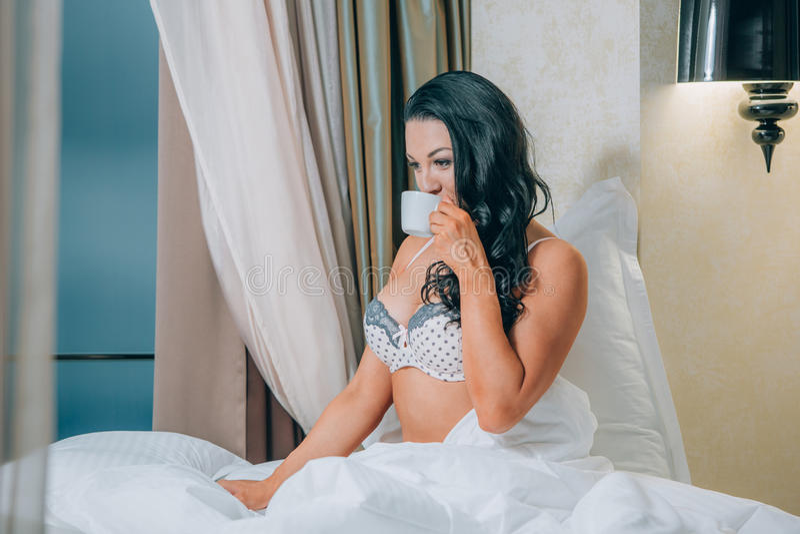 Portrait de belle jeune femme dans les chemises de nuit tenant la tasse de café sur le lit photo libre de droits