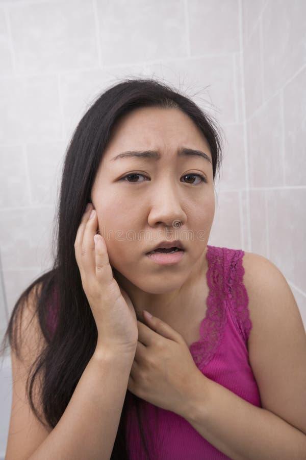 Portrait de belle jeune femme examinant son visage dans la salle de bains images libres de droits