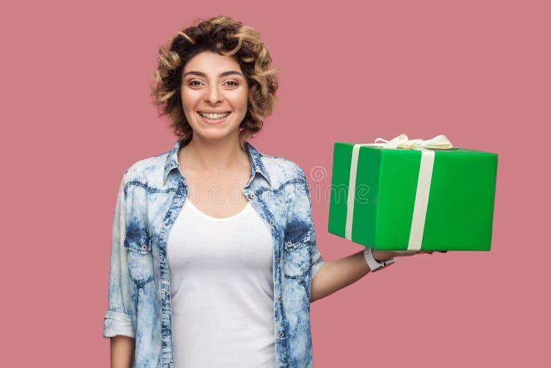 Portrait de belle jeune femme heureuse dans la chemise bleue avec la coiffure curlty tenant et tenant le boîte-cadeau vert avec l images stock