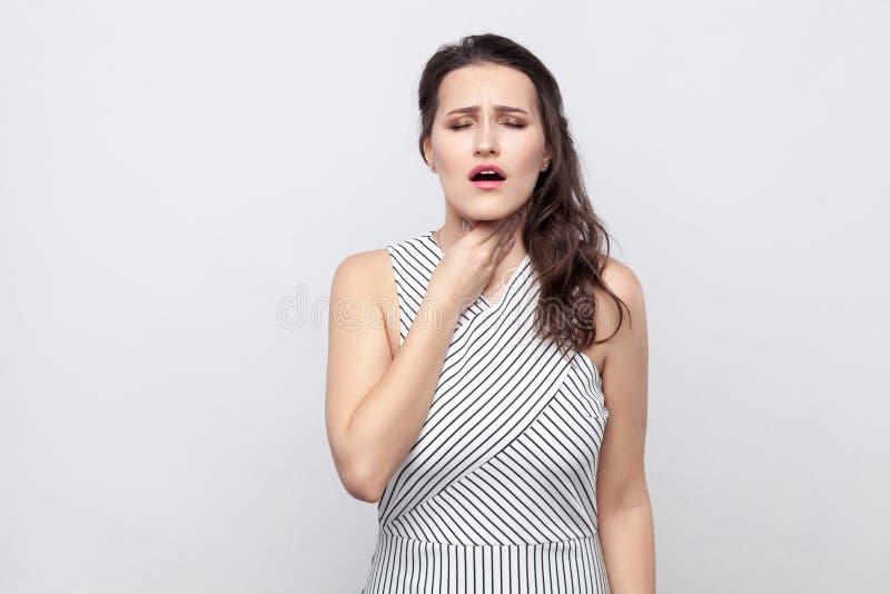 Portrait de belle jeune femme malade de brune avec le maquillage et la position rayée de robe tenant son cou et sentant la douleu photo libre de droits