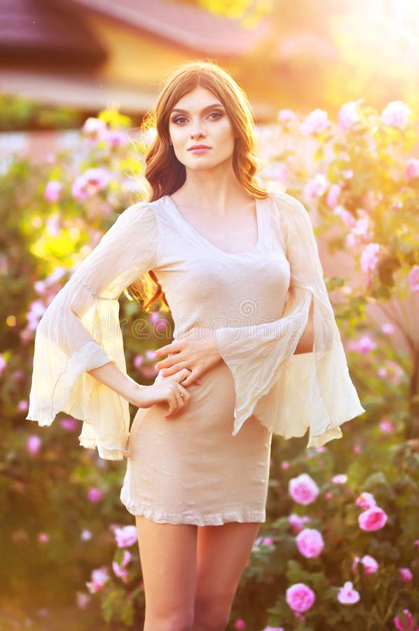 Portrait de belle jeune femme posant par le rosier photo libre de droits