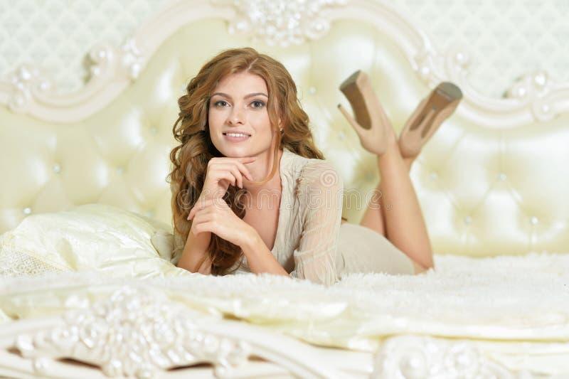 Portrait de belle jeune femme posant sur le lit ? la maison photo libre de droits