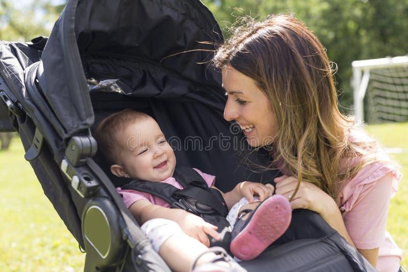 Portrait de belle jeune femme poussant la voiture d'enfant en parc photo libre de droits