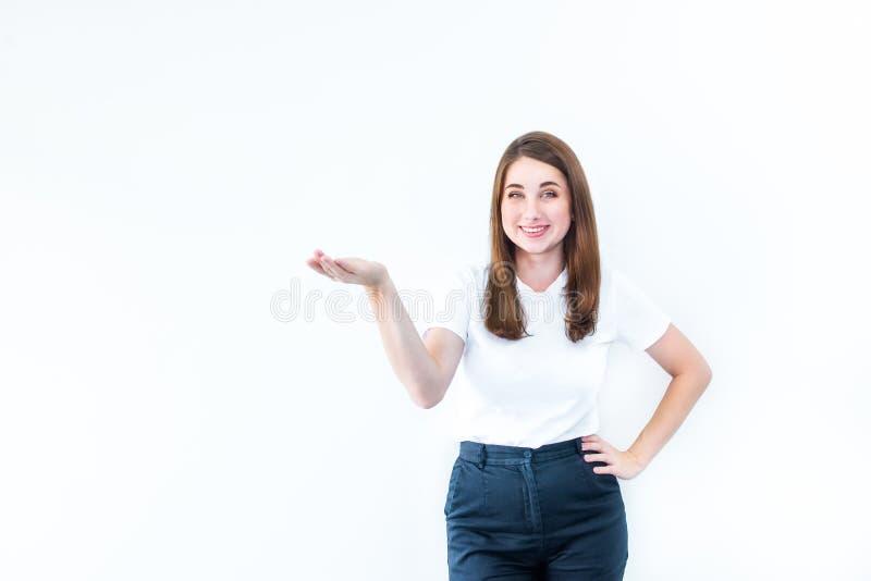 Portrait de belle jeune femme riante de brune dans le T-shirt occasionnel montrant l'espace vide de copie sur la paume ouverte de photographie stock
