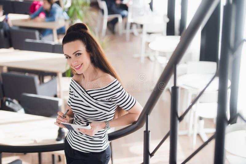 Portrait de belle jeune femme se tenant dans un café se penchant sur la balustrade et regardant le sourire d'appareil-photo réuss images libres de droits
