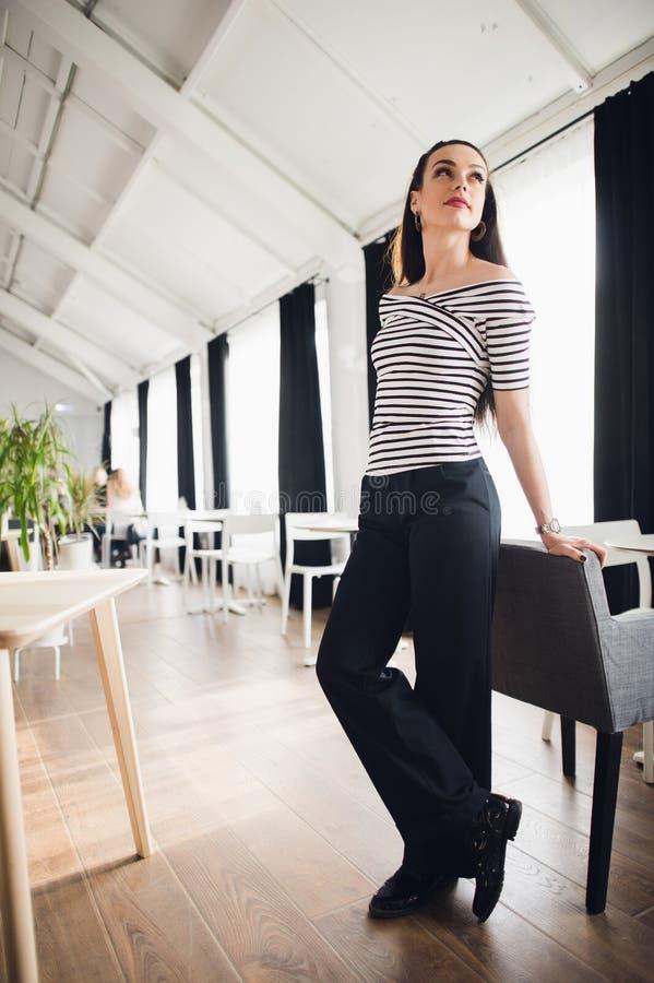 Portrait de belle jeune femme se tenant dans un café se penchant sur la chaise et regardant loin souriant Café femelle réussi images libres de droits