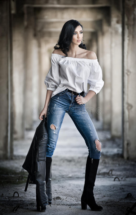 Portrait de belle jeune femme sexy avec l'équipement moderne, la veste en cuir, les jeans, le chemisier blanc et les bottes noire photographie stock libre de droits