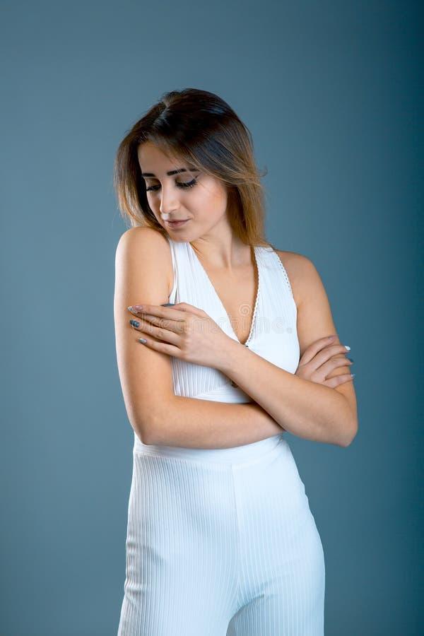 Portrait de belle jeune femme sexy avec la combinaison élégante, sur le fond de gris bleu Jeune brune attrayante avec la longue p photographie stock libre de droits