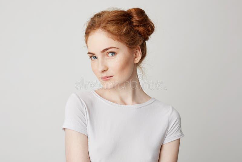 Portrait de belle jeune fille espiègle avec les cheveux rouges regardant l'appareil-photo au-dessus du fond blanc photo libre de droits