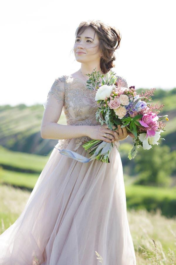 Portrait de belle jeune mariée avec le bouquet en nature Photographie de beaux-arts photos stock