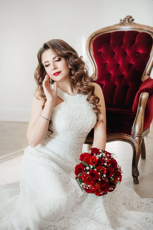 Portrait de belle jeune mariée dans la robe blanche avec le bouquet rouge photographie stock libre de droits