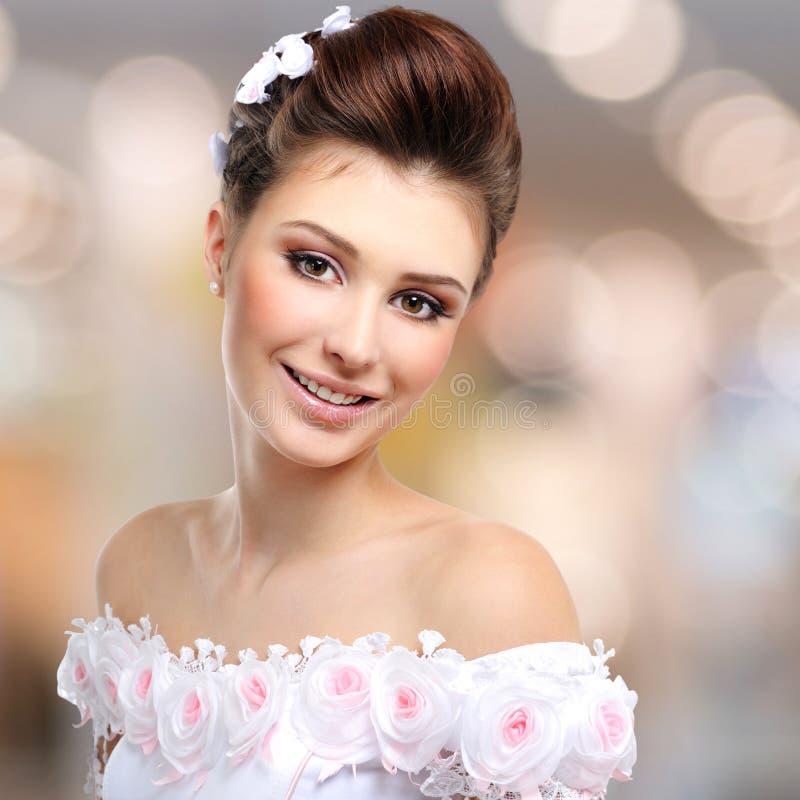 Portrait de belle jeune mariée de sourire dans la robe de mariage image stock