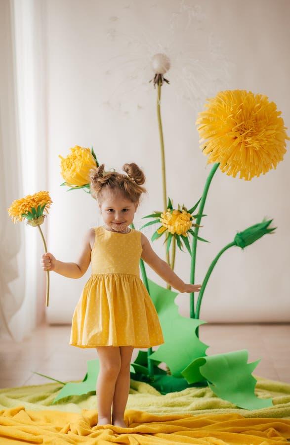 Portrait de belle petite fille avec le pissenlit et les tulipes jaunes images stock