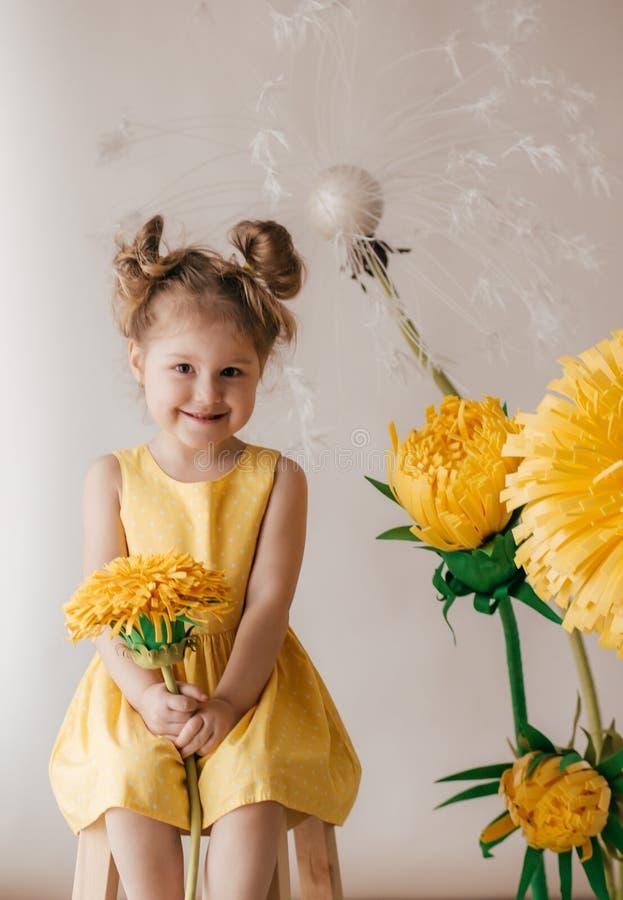 Portrait de belle petite fille avec le pissenlit et les tulipes jaunes image libre de droits