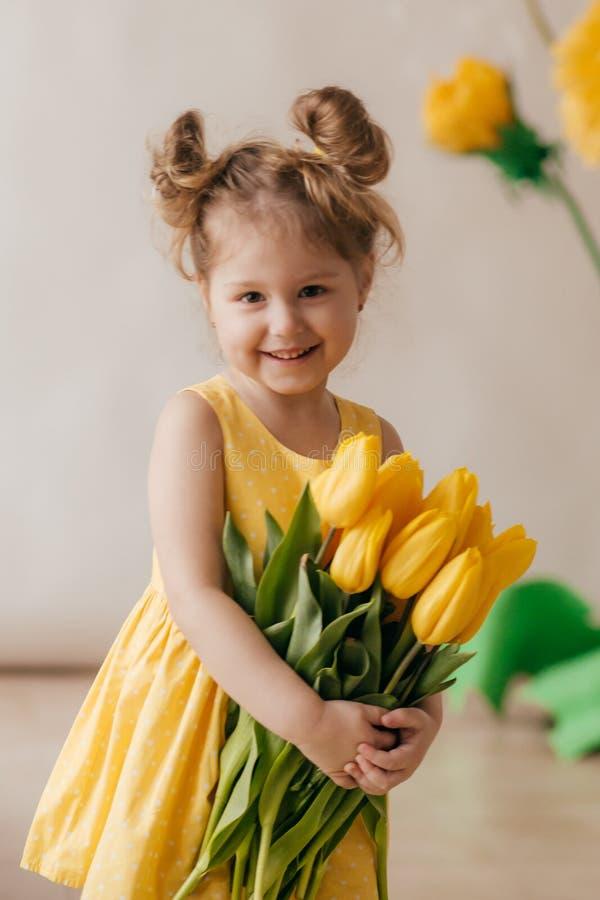 Portrait de belle petite fille avec le pissenlit et les tulipes jaunes photos stock
