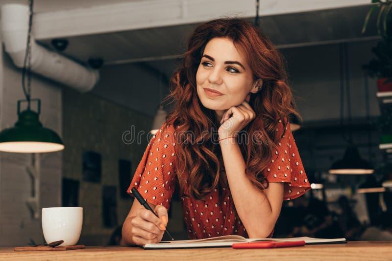 portrait de blogger songeur se reposant à la table avec le carnet photographie stock