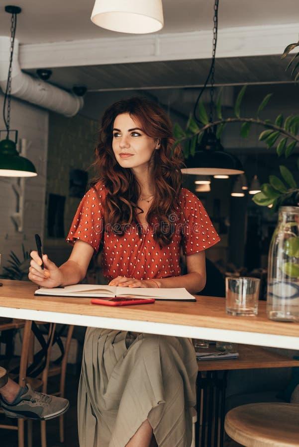 portrait de blogger songeur se reposant à la table avec le carnet image stock