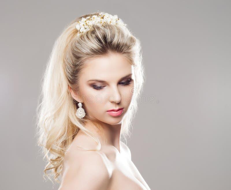 Portrait de blond magnifique avec un beau bandeau sur un b gris image libre de droits
