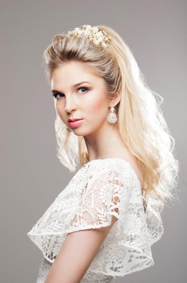 Portrait de blond magnifique avec un beau bandeau sur un b gris photo stock