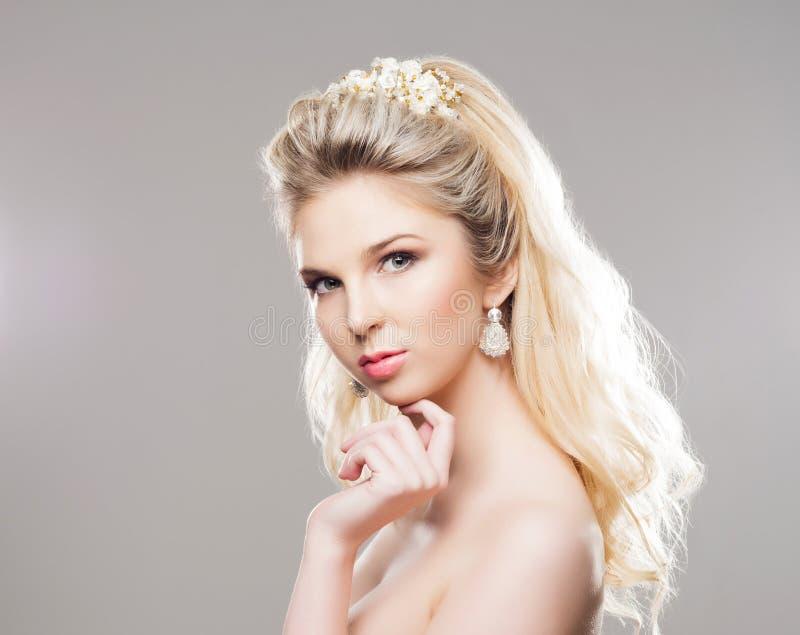 Portrait de blond magnifique avec un beau bandeau sur un b gris image stock