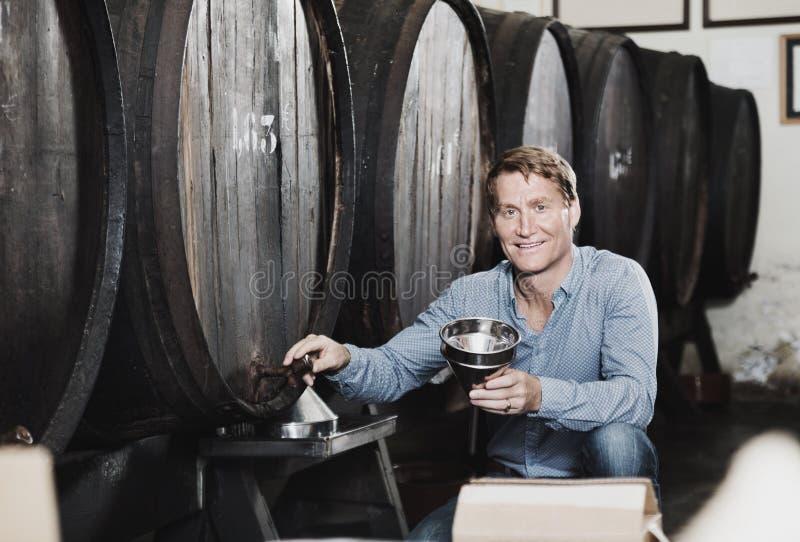 Portrait de boisson alcoolisée de versement de vendeur masculin de bois dans la bouteille photo stock