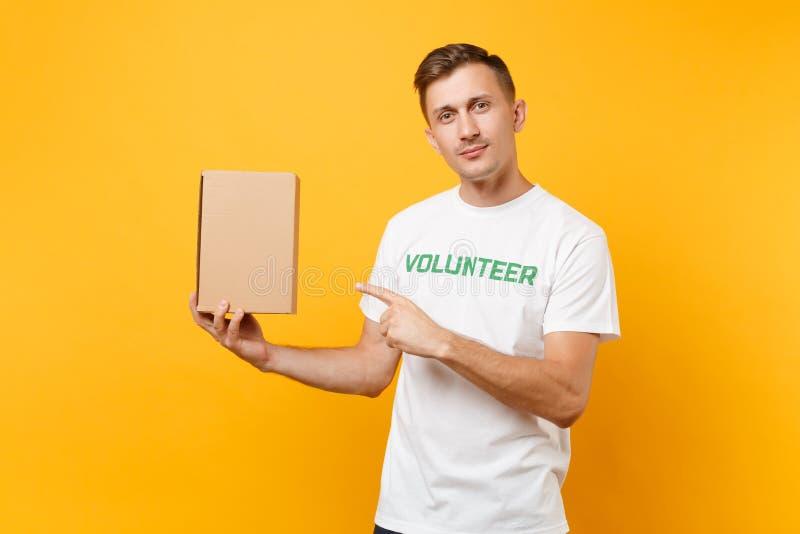 Portrait de bon homme aimable dans le T-shirt blanc avec le volontaire écrit de titre de vert d'inscription avec la boîte en cart photographie stock