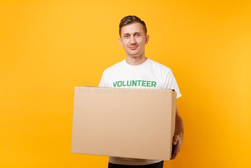 Portrait de bon homme aimable dans le T-shirt blanc avec le volontaire écrit de titre de vert d'inscription avec la grande boîte  photos stock
