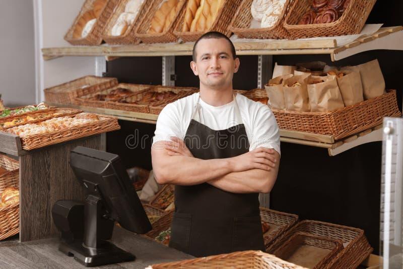 Portrait de boulanger professionnel au bureau de caissier près de l'étalage photos libres de droits