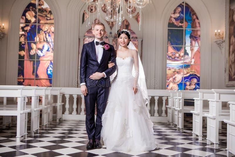 Portrait de bras debout de couples sûrs de mariage dans le bras à l'église photos stock