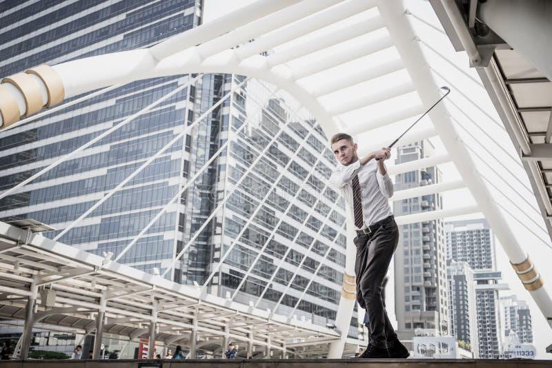 Portrait de Businessman jouant au golf avec le paysage urbain en arrière-plan image libre de droits
