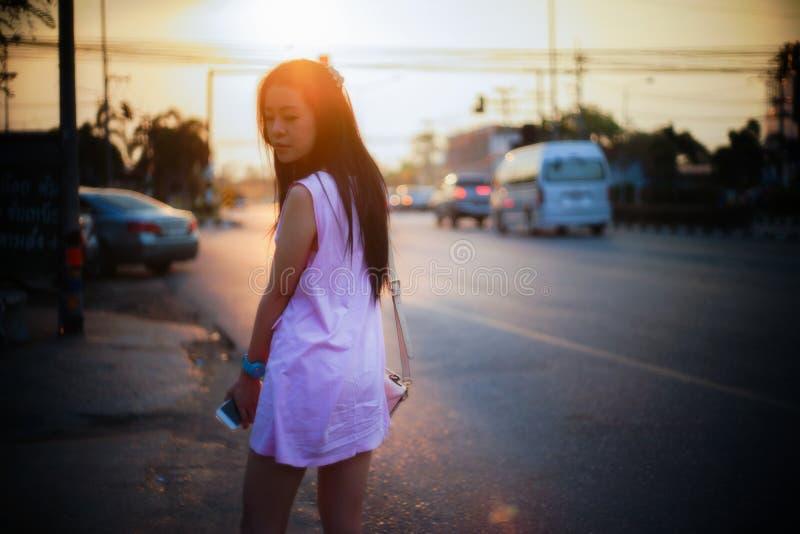 Portrait de côté debout de jeune femme asiatique de rue au moment de coucher du soleil, image filtrée, foyer mou photos stock